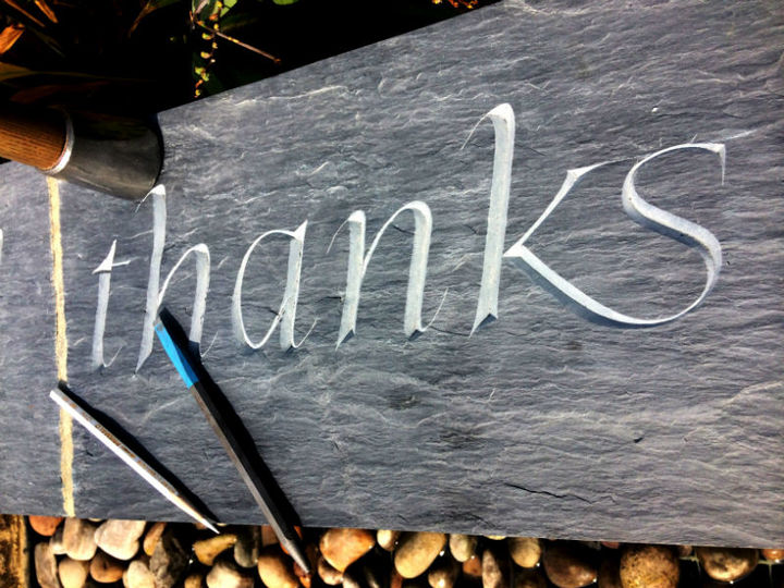 lettering carved in slate with the word thanks