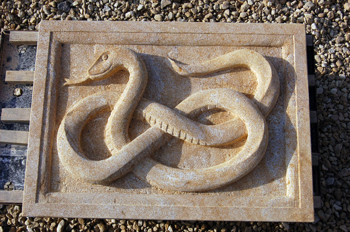 heraldic carving of snake in ham stone on private house