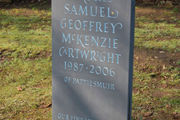 memorial for teenager in slate with gilded disc at the top and blue lettering