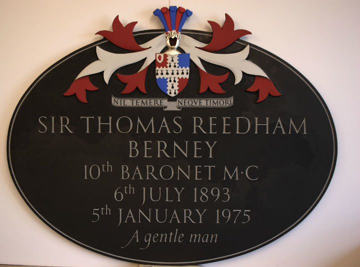 traditional oval church plaque with armorial carving at the top which has been painted