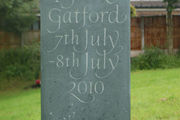 hand carved baby memorial with informal lettering in green slate
