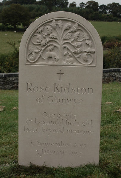 child memorial stone in Portland with carving in relief at the top