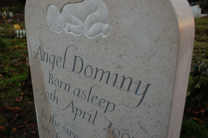 infant headstone with carving of a sleeping infant at the top