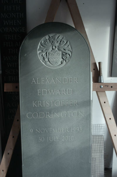 green slate headstone with coat of arms carved in relief at the top