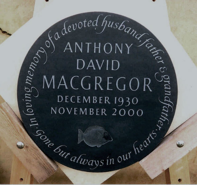 circular memorial plaque in slate with fish carving