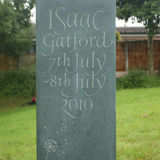 This bespoke child's headstone is carved from green slate with organic lettering.