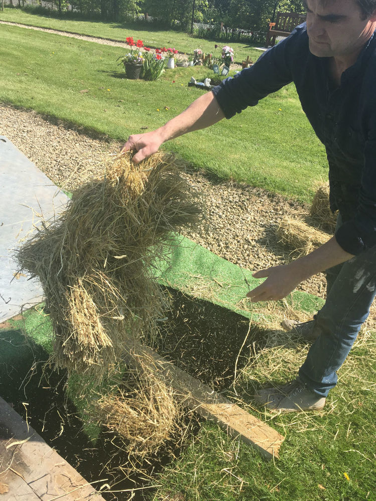 adding hay to grave
