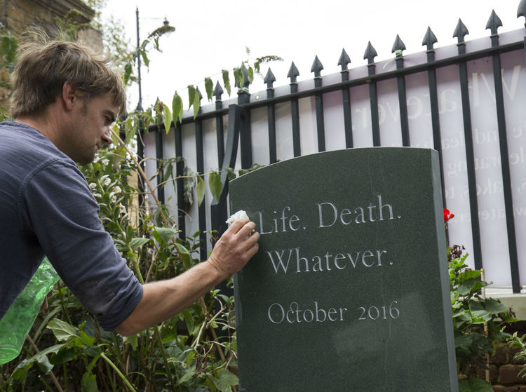 cleaning headstone at Sutton House