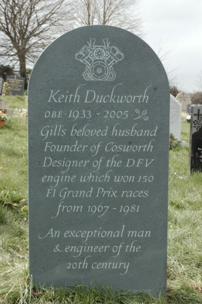 green slate headstone with line carving at the top